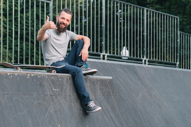 Uśmiechnięty brodaty hipster siedzi na rampie i pokazuje znak shaka.