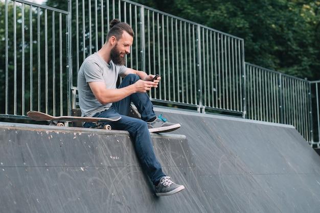Uśmiechnięty brodaty hipster siedzi na rampie i przegląda smartfona.