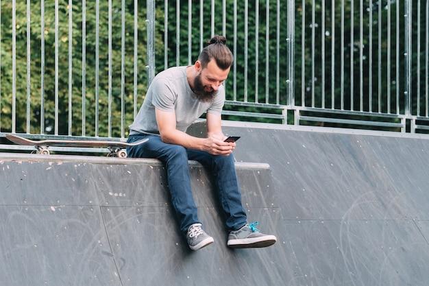 Uśmiechnięty brodaty hipster siedzi na rampie z deskorolką i przegląda smartfona.