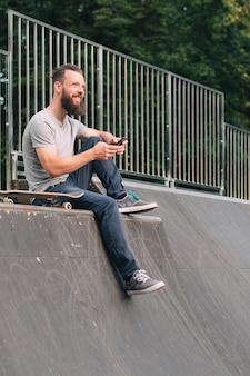 Uśmiechnięty brodaty hipster siedzi na rampie z deskorolką i smartfonem.