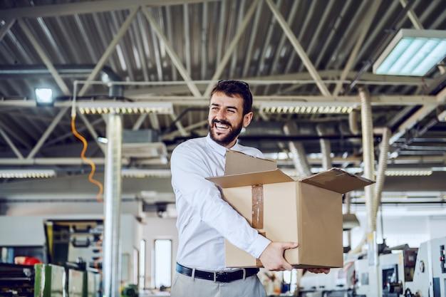 Uśmiechnięty brodaty inżynier grafiki w koszuli i krawacie, chodzenie w drukarni i przenoszenie pudełka