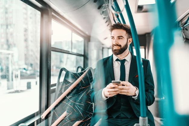 Uśmiechnięty brodaty kaukaski biznesmen w formalnej odzieży siedzi publicznie transport i używa mądrze telefon.