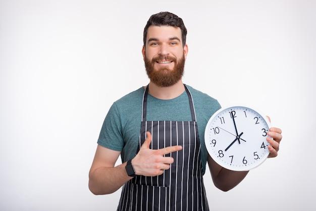 Uśmiechnięty brodaty mężczyzna jest ubranym fartucha trzyma białego zegar podczas gdy ono uśmiecha się na biel ścianie