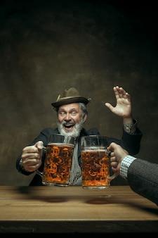 Uśmiechnięty brodaty mężczyzna pije piwo w pubie