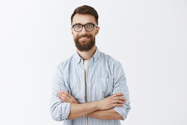 Uśmiechnięty brodaty mężczyzna pozowanie na białej ścianie