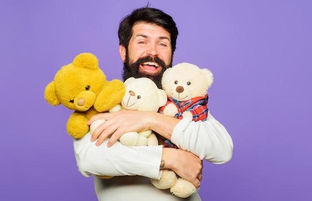 Uśmiechnięty brodaty mężczyzna przytula misie. szczęśliwy brodaty mężczyzna z pluszowymi zabawkami. prezent i prezent.