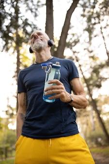 Uśmiechnięty brodaty mężczyzna relaksuje się po treningu na świeżym powietrzu