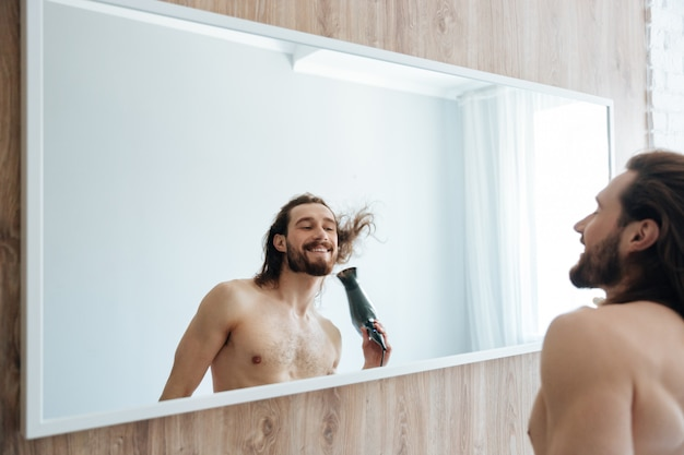 Uśmiechnięty brodaty mężczyzna suszy włosy z suszarką do włosów blisko lustra