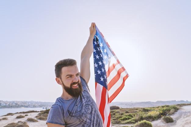 Uśmiechnięty brodaty mężczyzna trzyma w podniesionej ręki flaga amerykańskiej