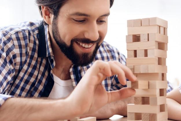 Uśmiechnięty brodaty mężczyzna usuwa drewniane klocki z wieży.