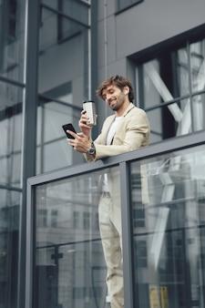 Uśmiechnięty brodaty mężczyzna w garniturze trzyma kawę na wynos i rozmawia z kolegami za pośrednictwem połączenia wideo