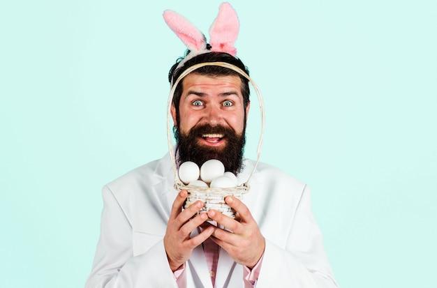 Uśmiechnięty brodaty mężczyzna w garniturze z koszem jaj. przygotowanie do wielkanocy. polowanie na jajka. święta wielkanocne.