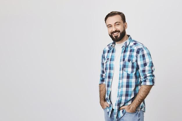 Uśmiechnięty brodaty mężczyzna w średnim wieku stojący na szarym tle