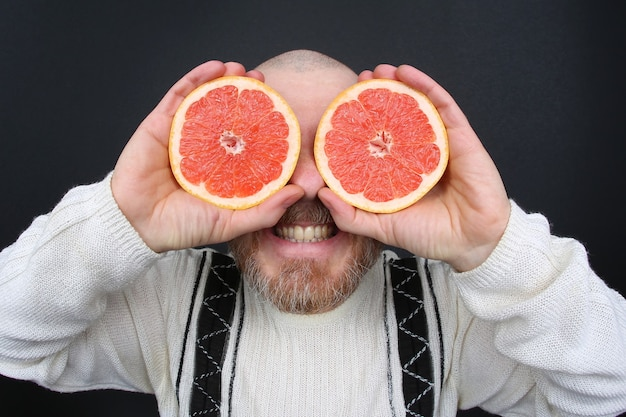 Uśmiechnięty brodaty mężczyzna z ciętym grejpfrutem w dłoniach
