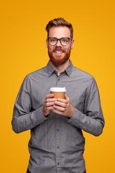 Uśmiechnięty brodaty mężczyzna z kawą na wynos