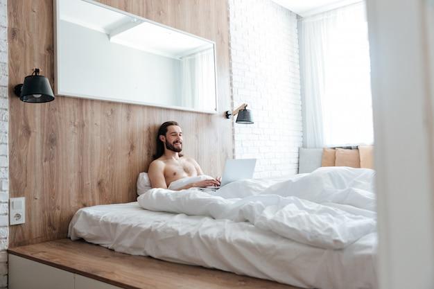 Uśmiechnięty brodaty młody człowiek siedzi laptop w łóżku i używa