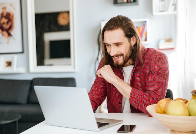Uśmiechnięty brodaty młody człowiek używa laptop w domu