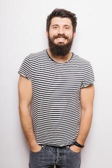 Uśmiechnięty brodaty młody model mężczyzna ubrany niedbale, na białym tle nad białą ścianą.