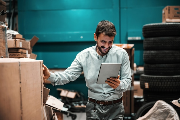 Uśmiechnięty, brodaty przełożony patrząc na tablet i sprawdzając pudełko gotowe do wysyłki. firma eksportowa.