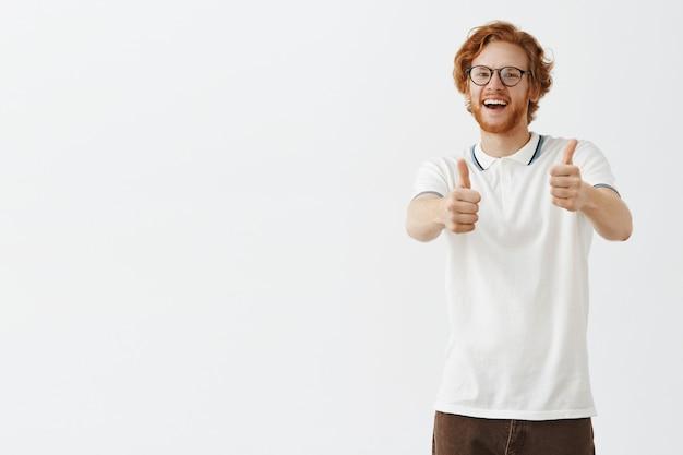 Uśmiechnięty brodaty rudy facet pozuje przy białej ścianie w okularach
