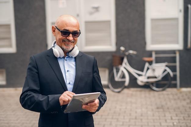 Uśmiechnięty brodaty starszy dorosły w kostiumu używać nowe technologie podczas gdy stojący na ulicie.