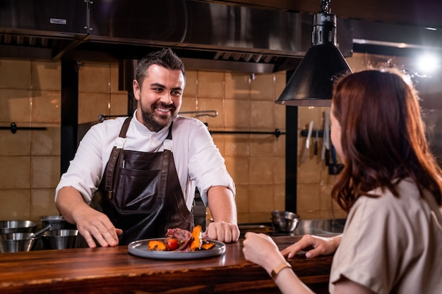 Uśmiechnięty brodaty szef kuchni w fartuchu, stojący przy ladzie i rozmawiający z kobietą, prezentując jej danie