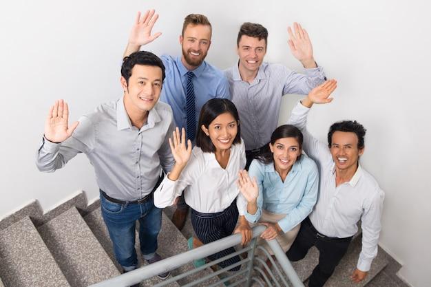 Uśmiechnięty business team salutowania na urząd schody