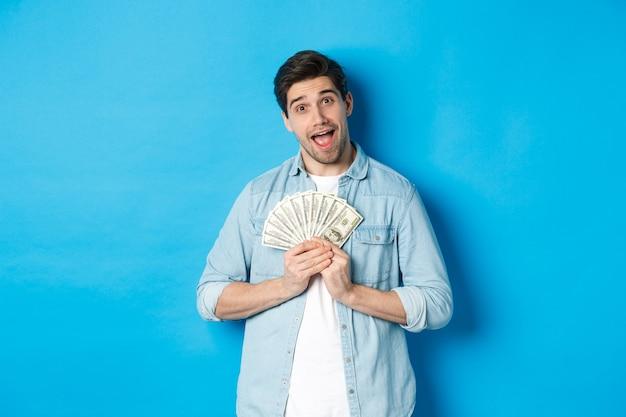 Uśmiechnięty chciwy facet przytulający pieniądze i uśmiechnięty, nie chcący się dzielić, stojący na niebieskim tle.