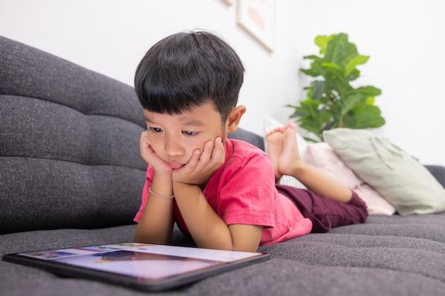 Uśmiechnięty chłopczyk patrzy na touchpad leżący na wygodnej kanapie w salonie