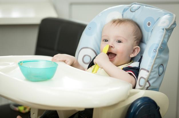 Uśmiechnięty chłopczyk siedzi w krzesełku i je kleik z łyżki