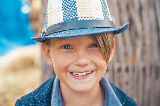 Uśmiechnięty chłopiec bawi się liśćmi i patrząc na kamery.
