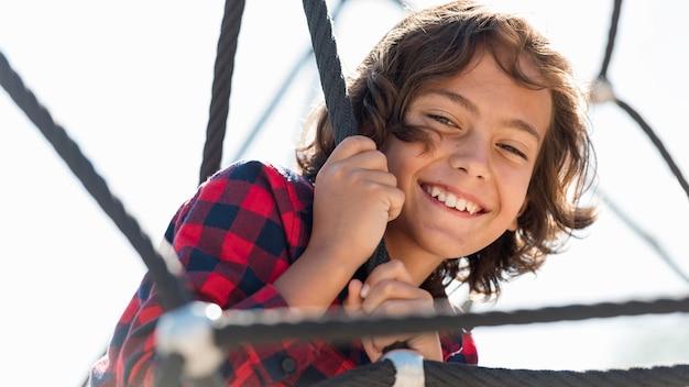 Uśmiechnięty chłopiec bawi się na świeżym powietrzu, podczas gdy z rodzicami