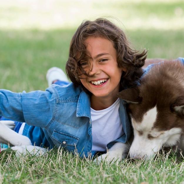 Uśmiechnięty chłopiec bawi się z psem w parku