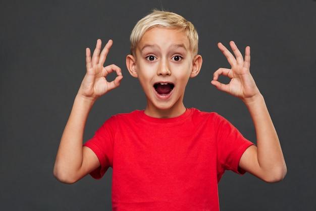 Uśmiechnięty chłopiec dziecko pokazuje zadowalającego gest.