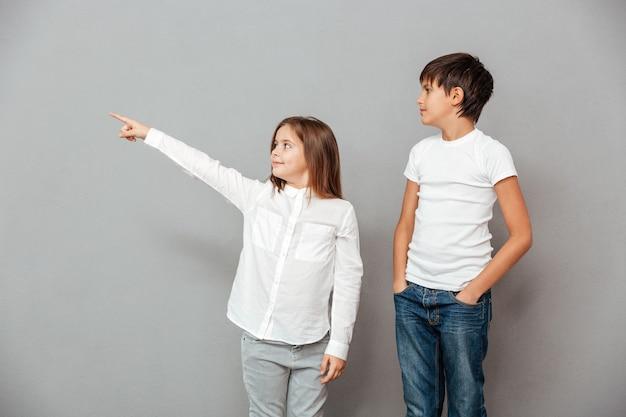 Uśmiechnięty chłopiec i dziewczynka, patrzący i wskazujący w bok .