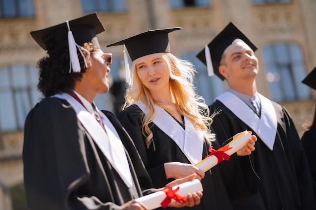 Uśmiechnięty chłopiec i dziewczynka w sukniach ukończenia szkoły i czapki mistrzów, rozmawiając podczas ich ukończenia szkoły