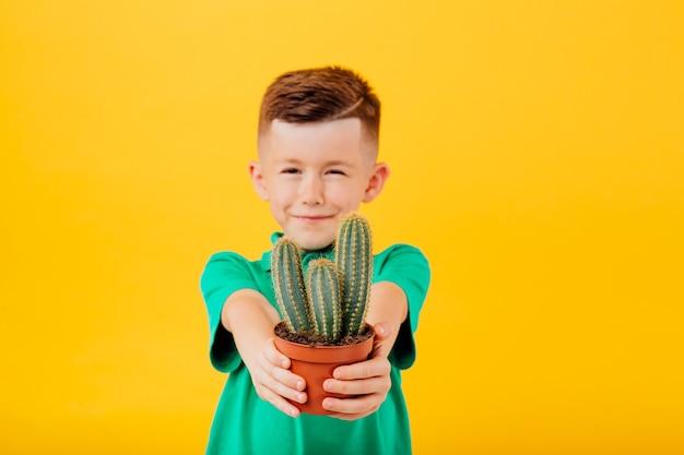 Uśmiechnięty chłopiec kaukaski trzyma kaktusa na białym tle na żółtym tle kopii przestrzeni w studio