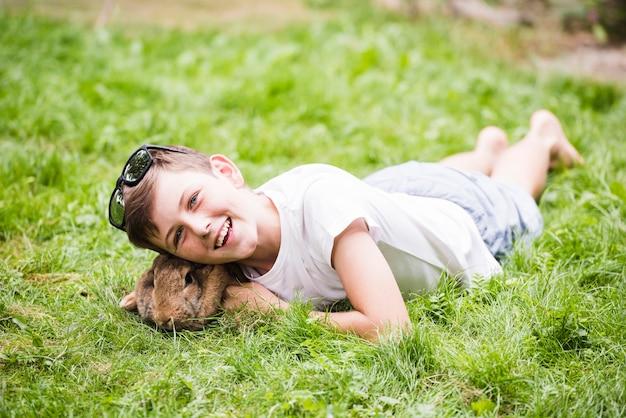 Uśmiechnięty chłopiec lying on the beach z królikiem na zielonej trawie w parku