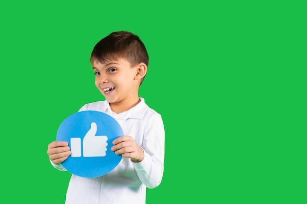 Uśmiechnięty chłopiec maluch pozuje z okrągłym sztandarem z kciukiem do góry