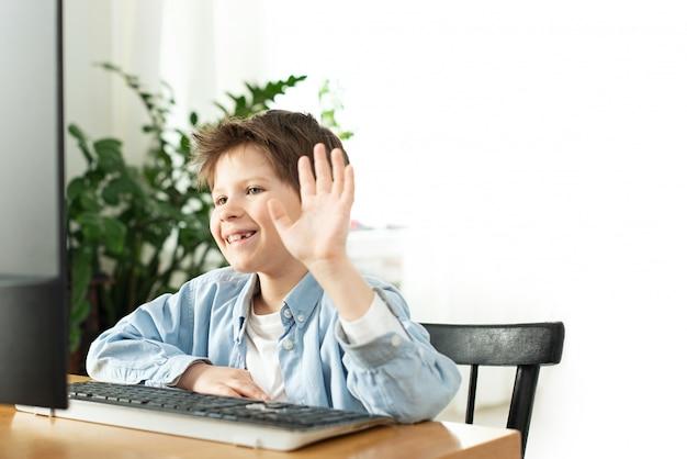 Uśmiechnięty chłopiec na czacie online i macha na ekranie komputera. dzieci i gadżety. uczenie się na odległość podczas izolacji w kwarantannie. chłopiec i laptop w domu. styl życia