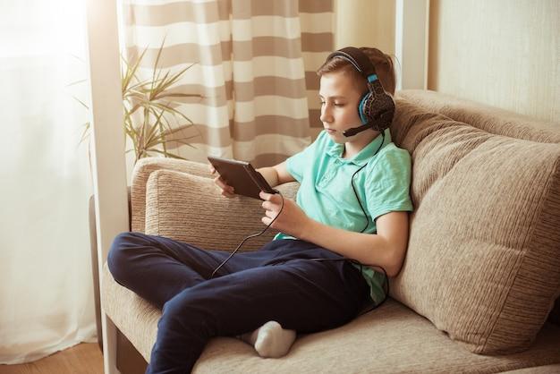 Uśmiechnięty chłopiec odrabia lekcje w słuchawkach iz tabletem. kształcenie na odległość w kwarantannie