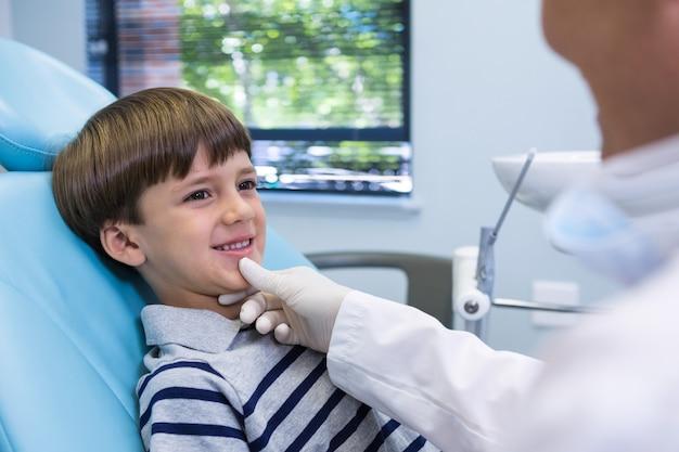 Uśmiechnięty chłopiec patrząc na dentystę siedząc na krześle