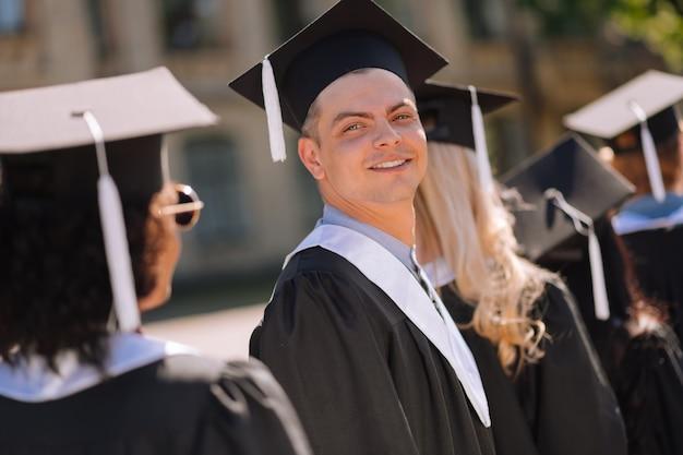 Uśmiechnięty chłopiec patrząc wstecz obok swoich przyjaciół absolwentów