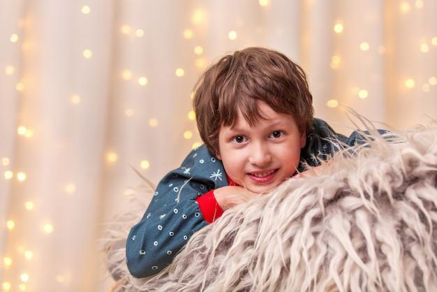 Uśmiechnięty chłopiec patrzy na choinkę w światełkach, a okno z girlandą otacza wakacyjny klimat