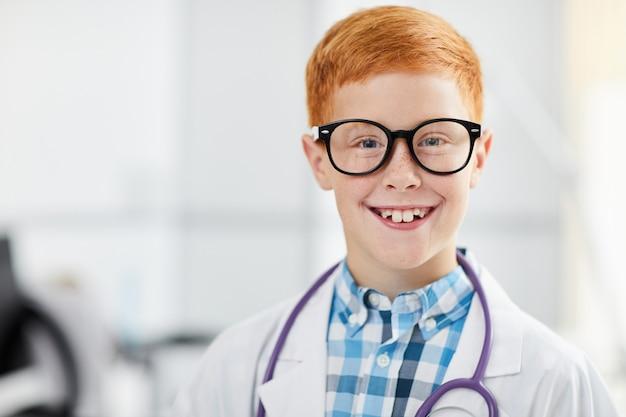 Uśmiechnięty chłopiec pozowanie jako lekarz