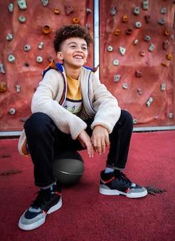 Uśmiechnięty chłopiec pozuje obok ściany wspinaczkowej