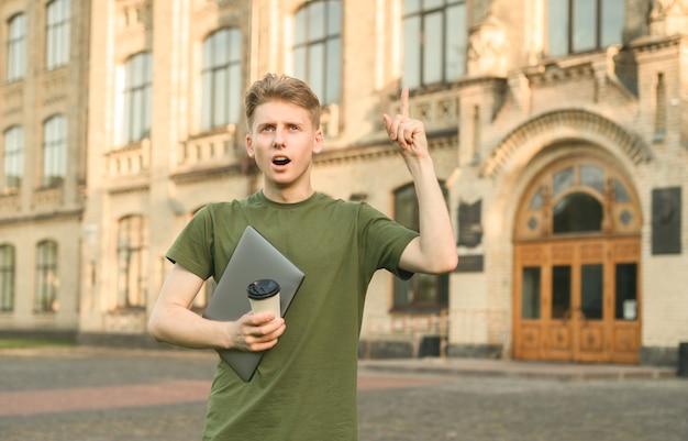 Uśmiechnięty chłopiec pozytywny student uniwersytetu w pobliżu kampusu z książkami