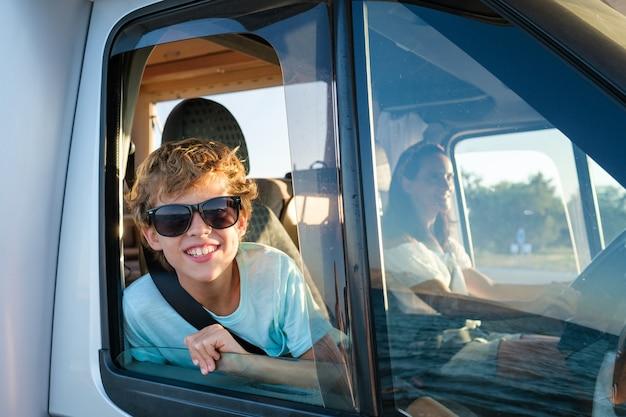 Uśmiechnięty chłopiec preteen w okularach przeciwsłonecznych wystający z otwartego okna samochodu kempingowego i patrzący na kamerę podczas podróży z matką podczas letnich wakacji