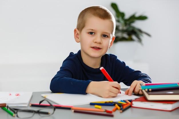 Uśmiechnięty chłopiec przy stole, rysowanie kredkami