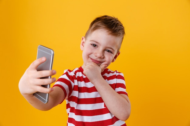 Uśmiechnięty chłopiec robi selfie i myśleć o czymś
